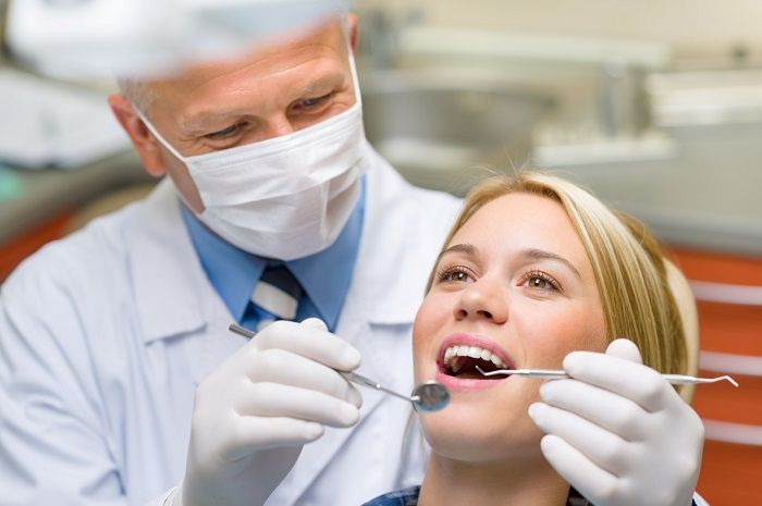 dentist doing quality control on dental crown